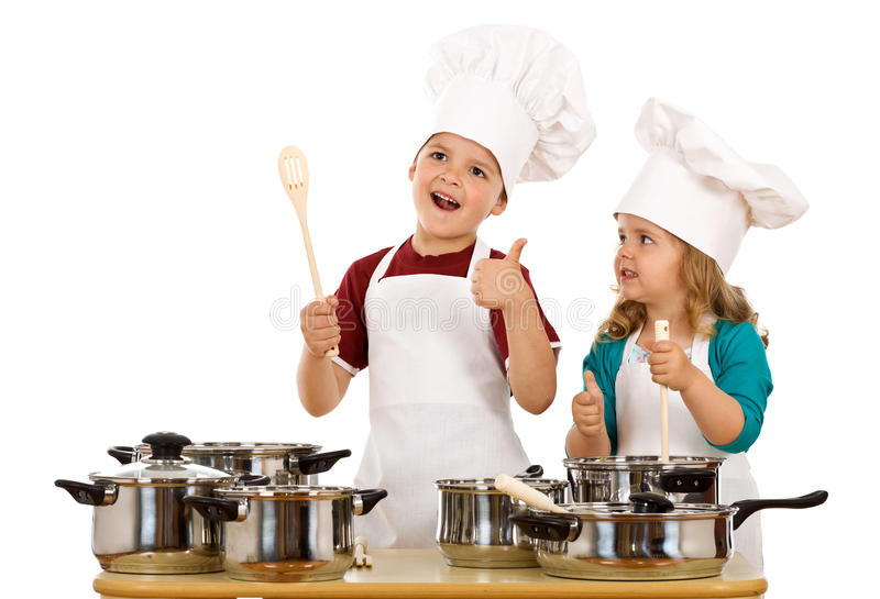 Happy chef and his aid - isolated. Happy satisfied chef and his aid - kids with cooking utensils, isolated stock photography