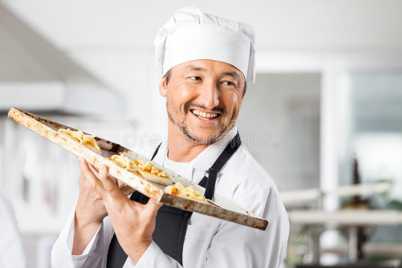 Happy Chef Holding Small Pizzas On Baking Sheet stock photos