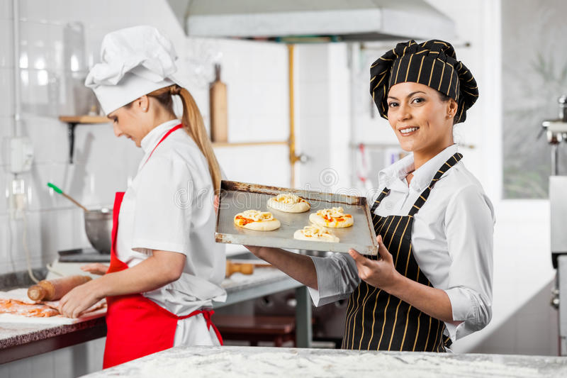 Happy Chef Holding Small Pizzas On Tray In Kitchen stock images