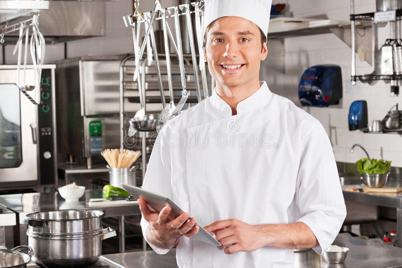 Happy Chef Holding Tablet Computer. Portrait of happy male chef holding tablet computer in commercial kitchen royalty free stock photos