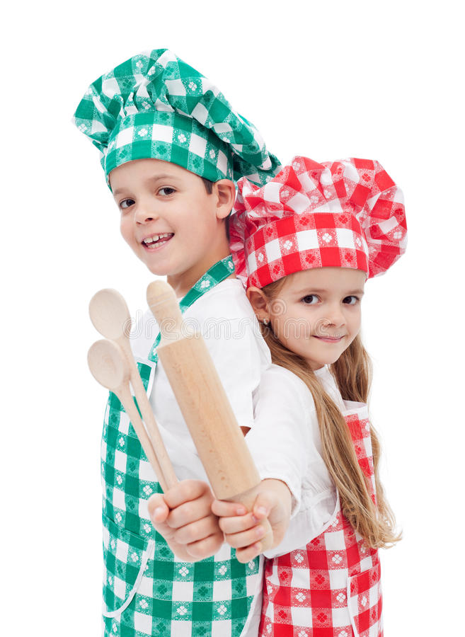 Happy chef kids with wooden cooking utensils. Happy chef kids holding wooden cooking utensils and smiling - isolated royalty free stock photography