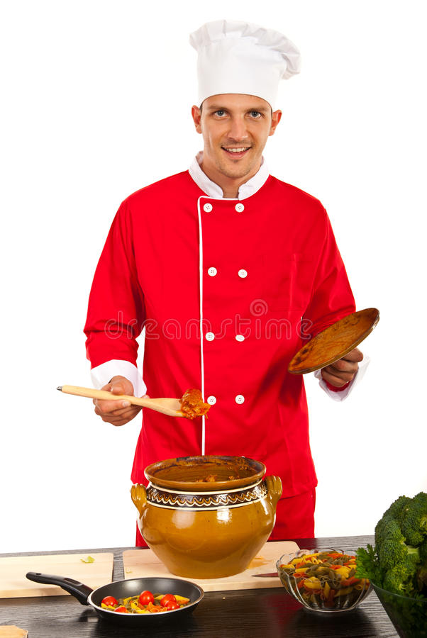 Happy chef man showing food. Happy chef mans howing food in big pot in kitchen royalty free stock images
