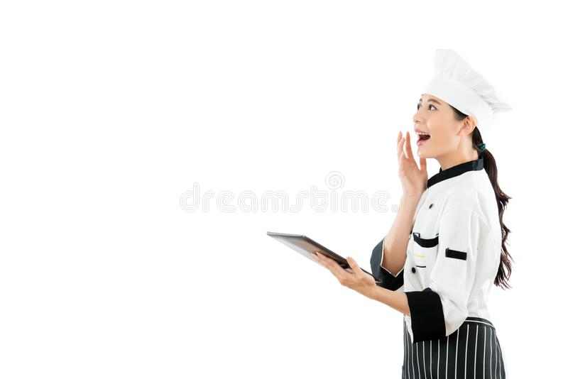 Happy chef opening the electronic menu online. Happy chef opening electronic menu online with digital tablet and projecting in blank area surprisingly watching stock photography