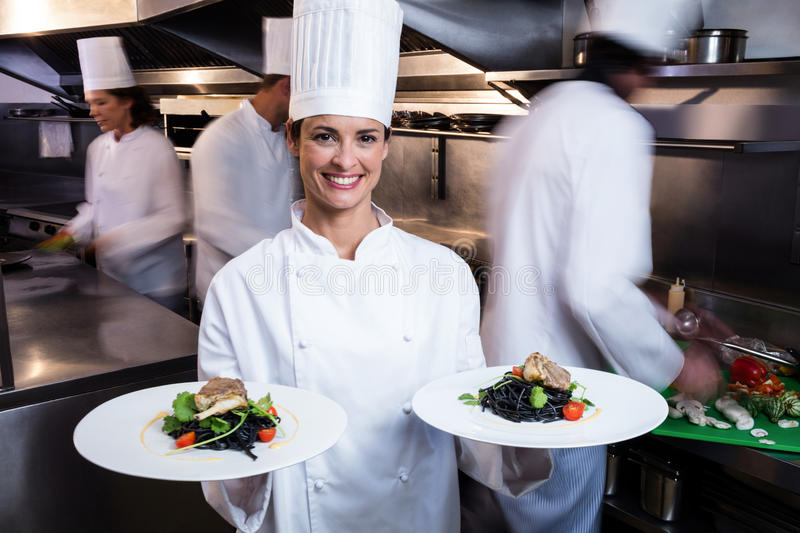 Happy chef presenting her food plates. In the commercial kitchen while team working behind her stock photo