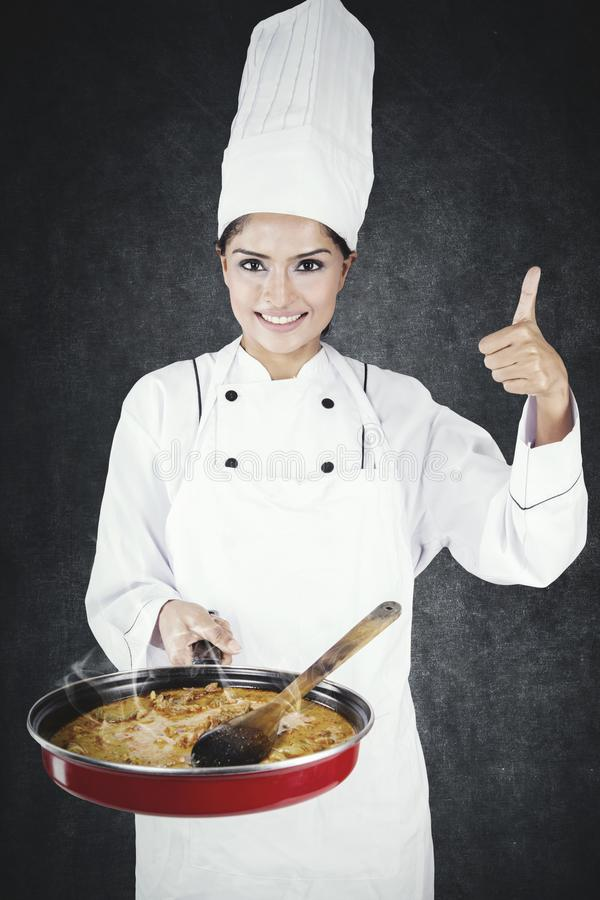 Happy chef shows thumb up and tasty food. Happy female chef showing thumb up and tasty food in a pan  while standing in the studio stock photos