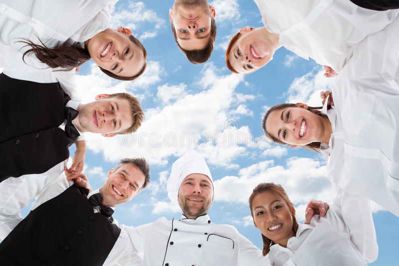 Happy chef and waiters standing in huddle against sky. Directly below portrait of happy chef and waiters standing in huddle against sky stock photos