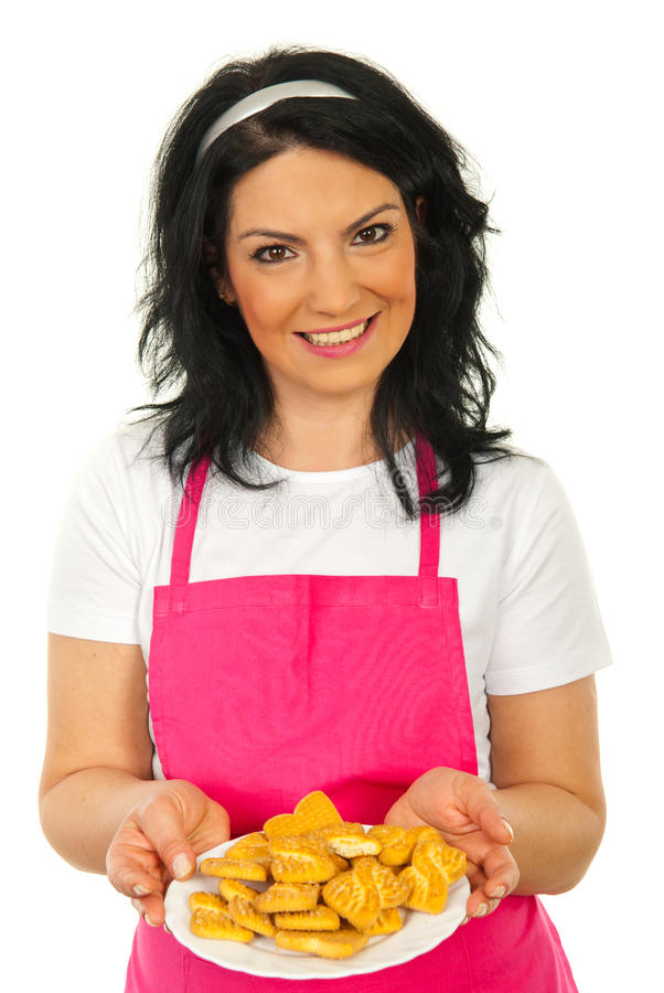 Happy chef woman showing biscuits. On plate isolated on white background stock photo