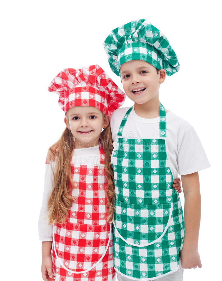 Happy chefs - boy and girl with aprons and hats. Happy chefs - boy and girl with aprons and cook hats, isolated royalty free stock photos