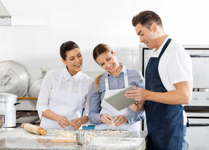 Happy Chefs Checking Recipe On Digital Tablet In stock image