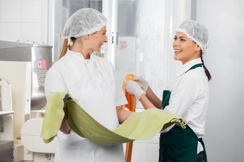 Happy Chefs Conversing While Holding Pasta Sheets royalty free stock photos
