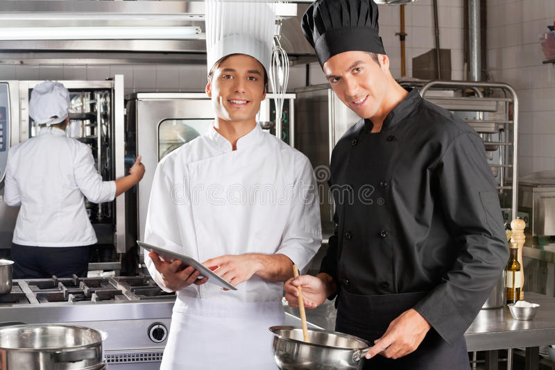 Happy Chefs Cooking Together. Portrait of happy chefs with digital tablet cooking in industrial kitchen stock photos
