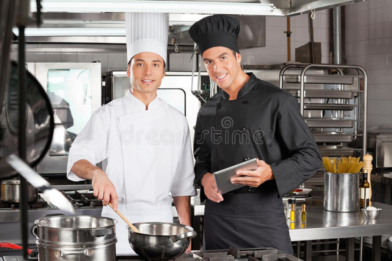 Happy Chefs With Digital Tablet Cooking Food royalty free stock image
