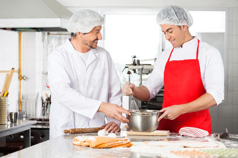 Happy Chefs Discussing While Preparing Ravioli royalty free stock image