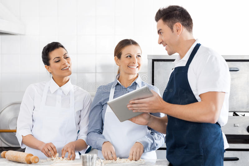 Happy Chefs Discussing Recipe On Digital Tablet In stock photo