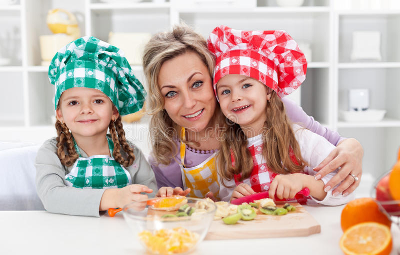 Happy chefs in the kitchen. Women and little girls portrait preparing fruit salad royalty free stock image
