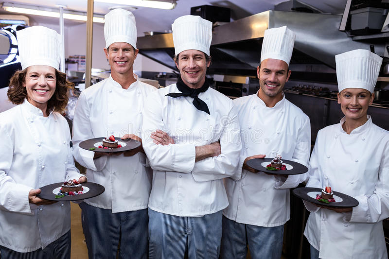 Happy chefs presenting their dessert plates royalty free stock photos
