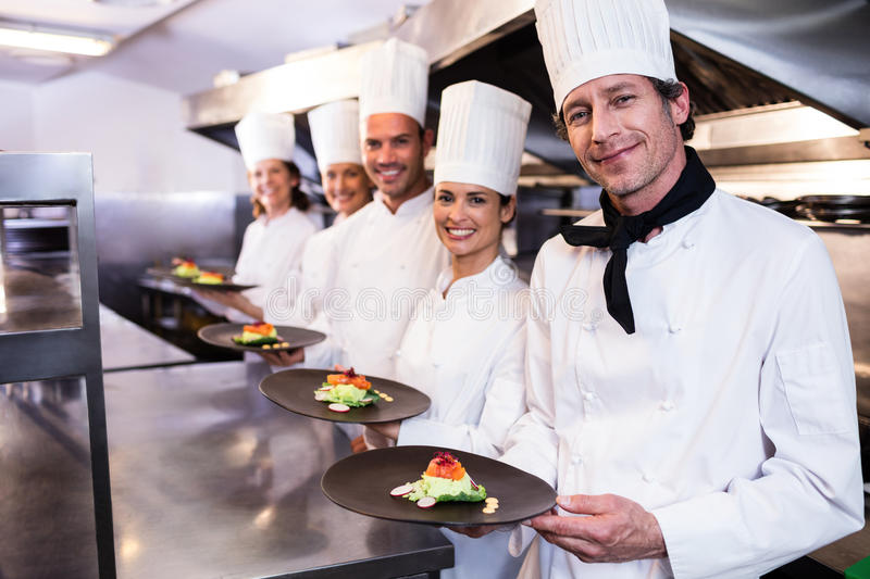 Happy chefs presenting their food plates royalty free stock photo