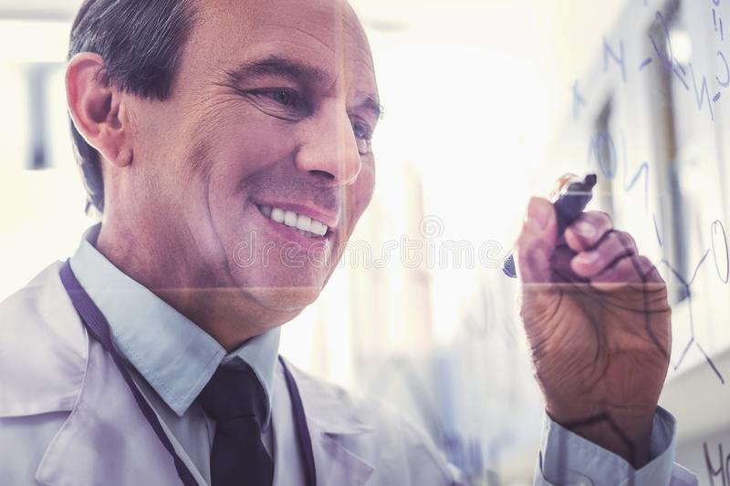 Happy chemist in process of new research. Process of research. Happy experienced skillful chemist feeling very busy being in process of new innovational research royalty free stock image