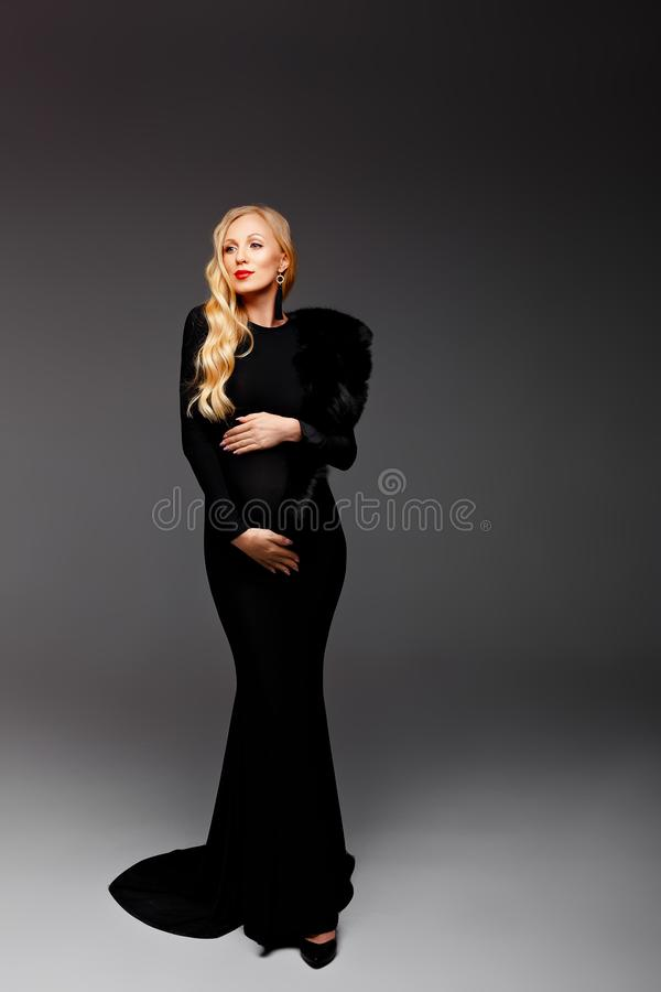Happy chic young pregnant woman in stylish black dress holding belly bump and posing in light. Stylish fashionable mom, hugging stock photos