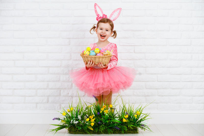 Happy chil in costume Easter bunny with eggs and green grass wit. Happy child girl in costume Easter bunny rabbit with ears and a basket of eggs and green grass stock photography