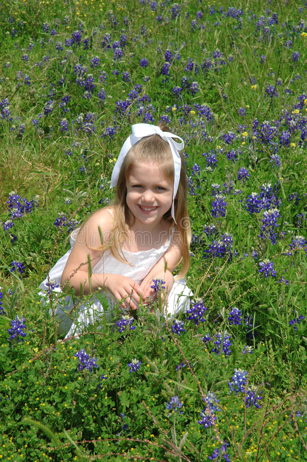 Happy Child. Bending down in a field of flowers. Blue Bonnets are native Texas flowers. The Blue Bonnet is the State Flower of Texas, USA stock photos