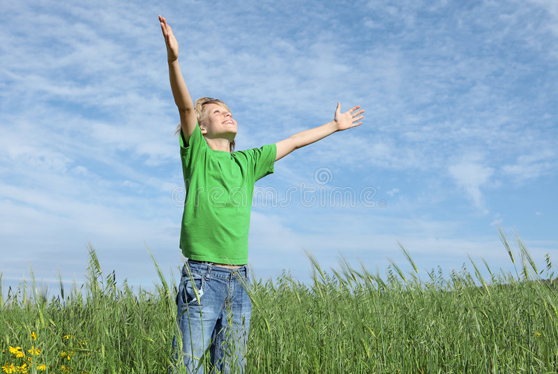 Happy child arms raised in prayer stock photography