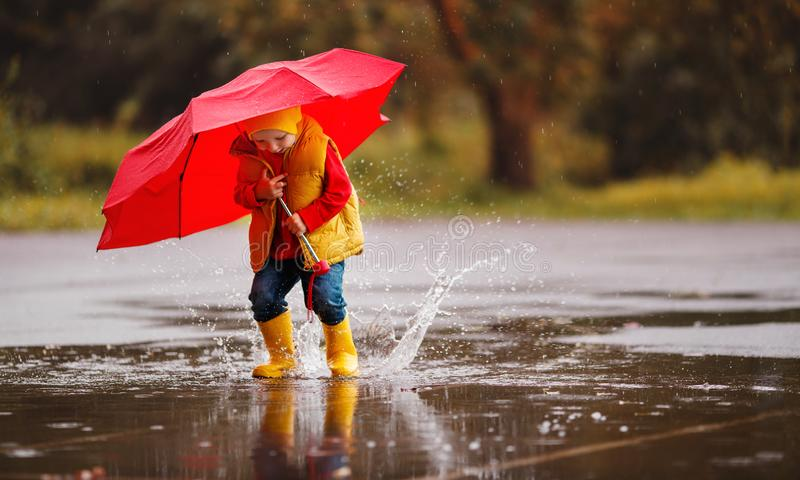 happy child baby boy with rubber boots and umbrella jump in puddle on autumn walk royalty free stock photos