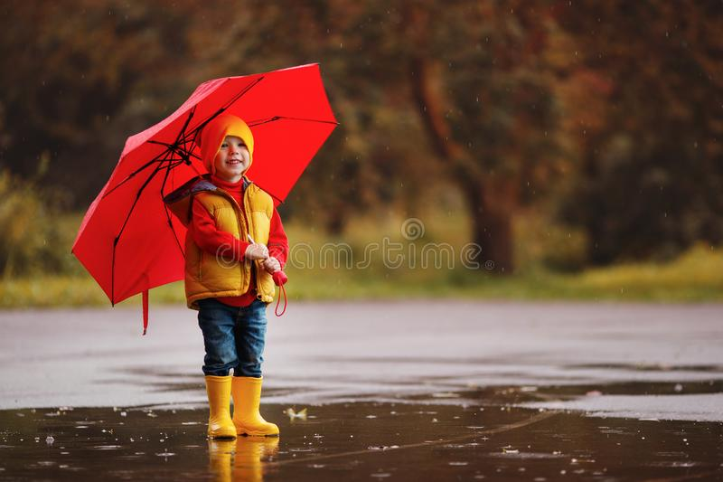 Happy child baby boy with rubber boots and umbrella jump in puddle on autumn walk. Happy child baby boy with rubber boots and umbrella jump in puddle on an stock photo
