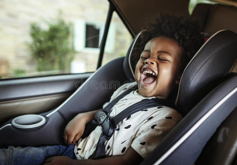 Happy child in a baby car seat royalty free stock photo