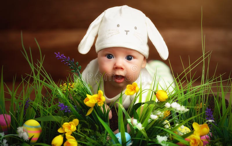 Happy child baby dressed as the Easter bunny rabbit on the grass. Happy child baby dressed as the Easter bunny rabbit lying on the grass on the lawn with flowers stock image