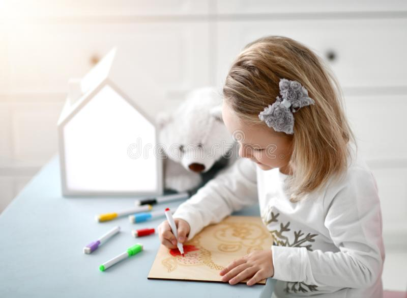 Happy child baby kid girl kindergarten drawing education with colorful markers at interior room stock photos