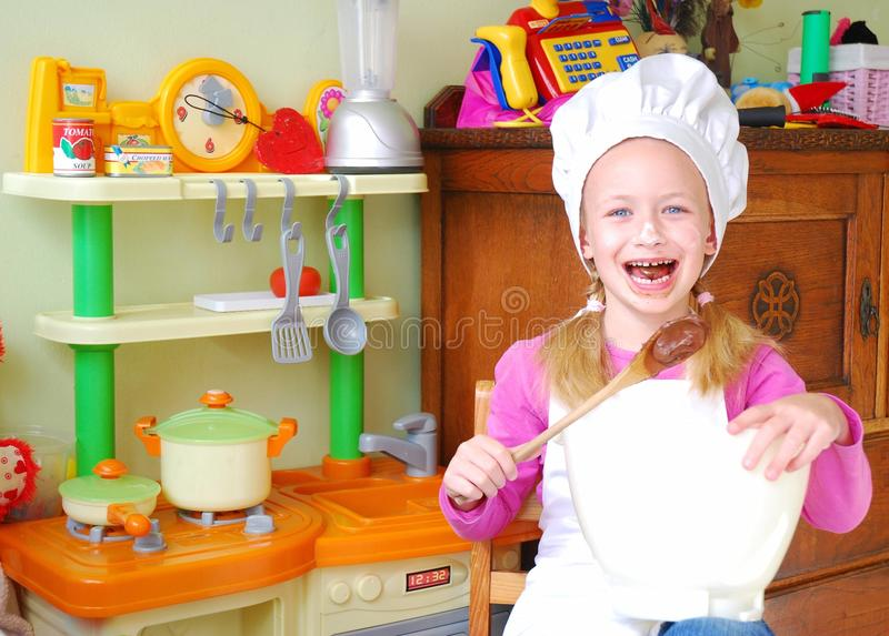 Happy child baker. Portrait of a beautiful cute little Caucasian girl child sitting in her play kitchen with happy laughing expression in her dirty face mixing royalty free stock photo