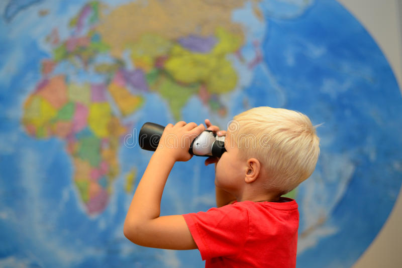 Happy child with binoculars are dreaming about traveling, journey. Tourism and travel concept. Creative background. stock images