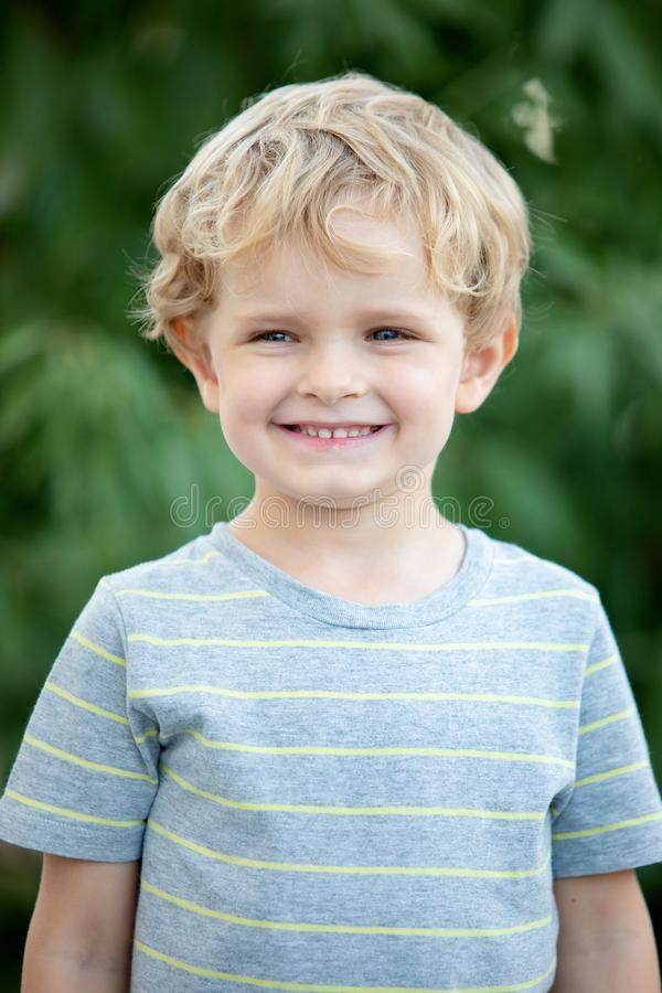 Happy child with blue t-shirt in the garden royalty free stock photos