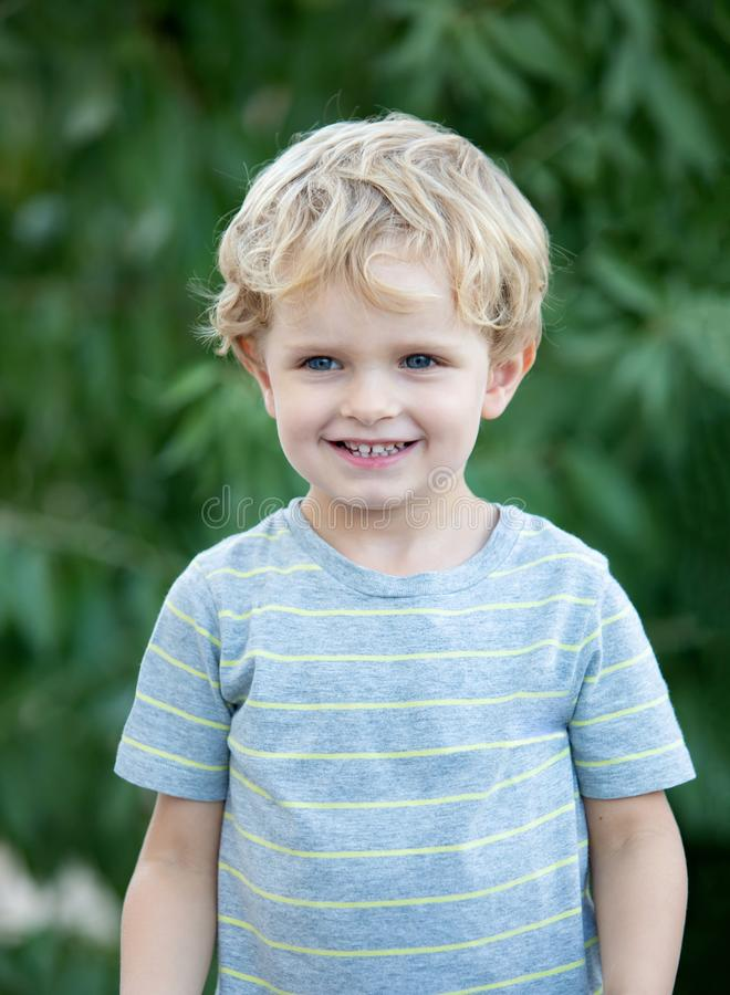Happy child with blue t-shirt in the garden stock image