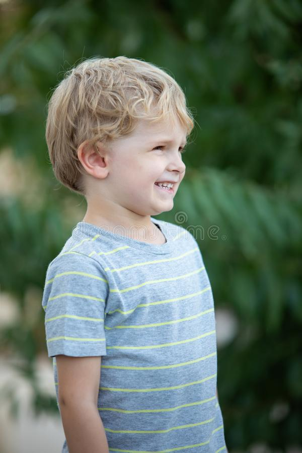 Happy child with blue t-shirt in the garden stock photo