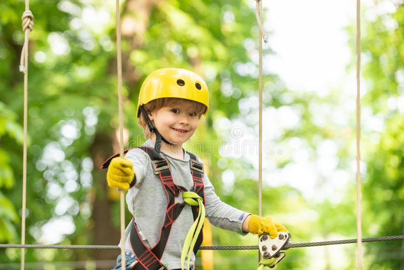 Happy child boy calling while climbing high tree and ropes. Portrait of a beautiful kid on a rope park among trees royalty free stock photography