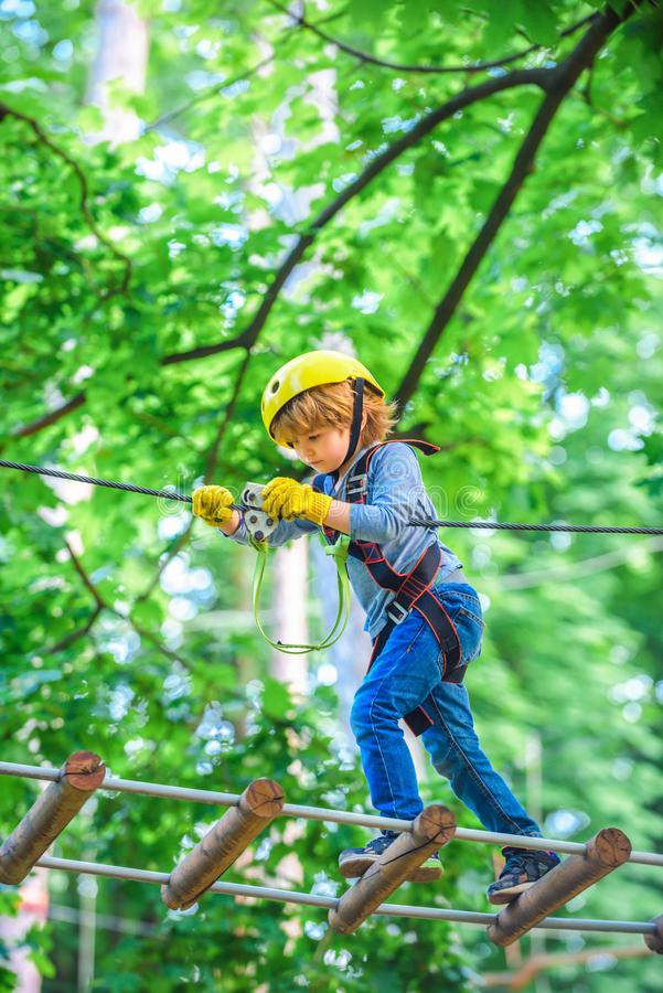 Happy child boy calling while climbing high tree and ropes. Child climbing on high rope park. Cute child boy. Toddler. Climbing in a rope playground structure stock photography