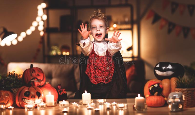 Happy child boy in costumes of vampire in a dark house in hallo stock images