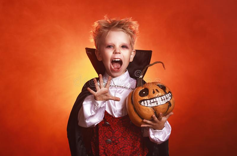 Happy child boy in costumes of vampire  in dark red background in halloween. Happy child  boy in costumes of vampire in a dark red background in   holiday royalty free stock photography