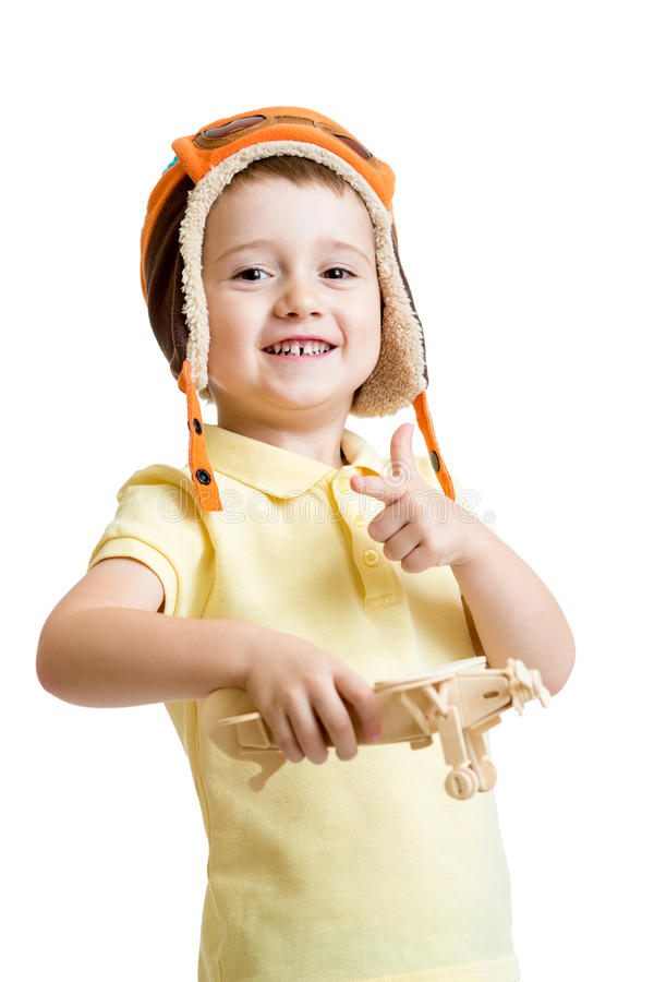 Happy child boy dressed pilot hat and playing with. Wooden airplane toy stock image