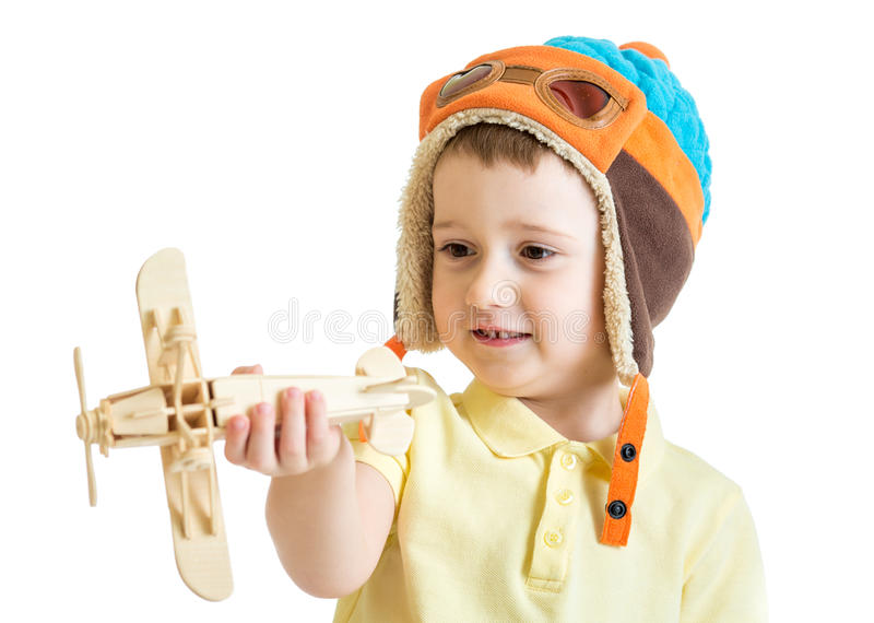 Happy child boy dressed pilot hat and playing with. Wooden airplane toy stock images