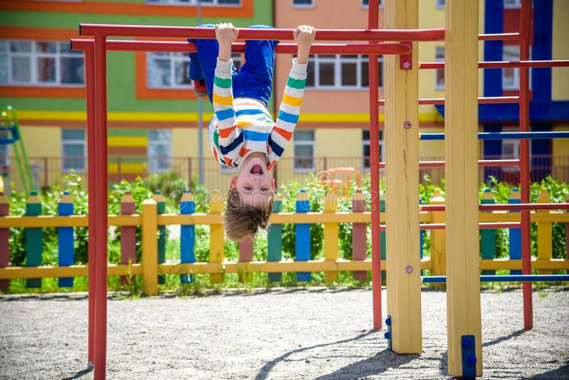 Happy child boy hanging upside down on bar, playground in city, outdoor activities.  stock image