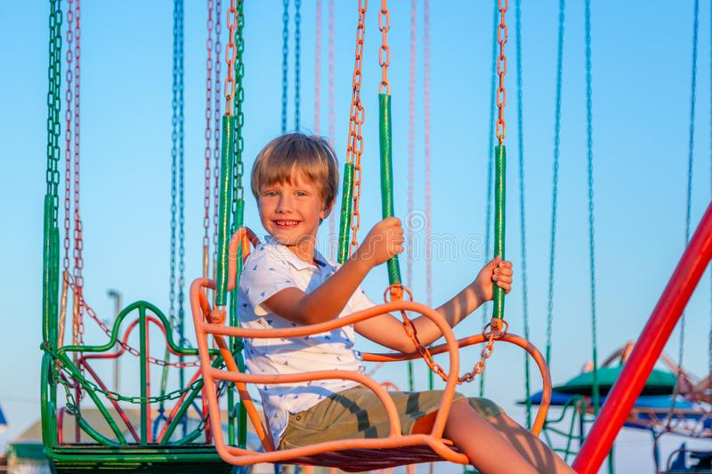 Happy child boy having fun in amusement park. Taking a ride on chain carousel. royalty free stock photos