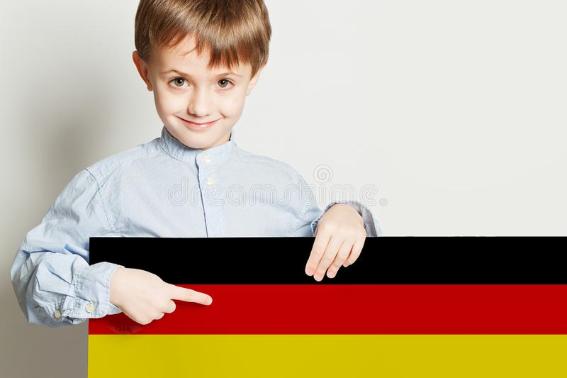 Happy child boy holding the Deutsch flag on white background stock images