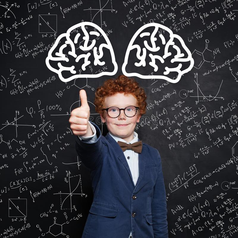 Happy child boy smiling and showing thumb up on science background stock photography