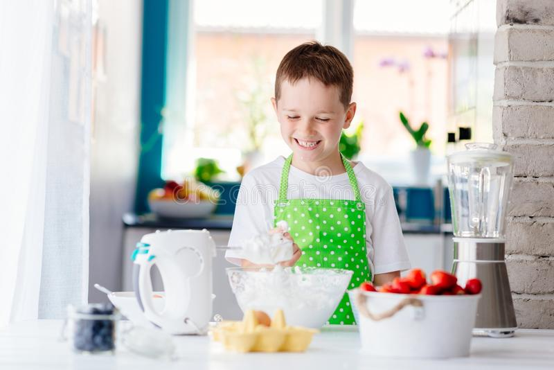 Happy child boy trying sweet dough and preparing a cake. stock image