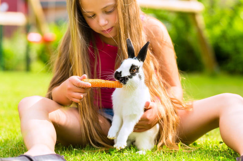 Happy child with bunny pet at home in garden. Happy Girl or daughter with her rabbit or bunny pet at home in the garden royalty free stock photos