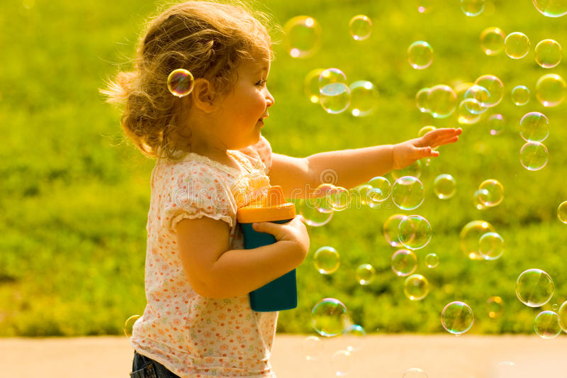Happy Child Chasing Soap Bubbles Royalty Free Stock