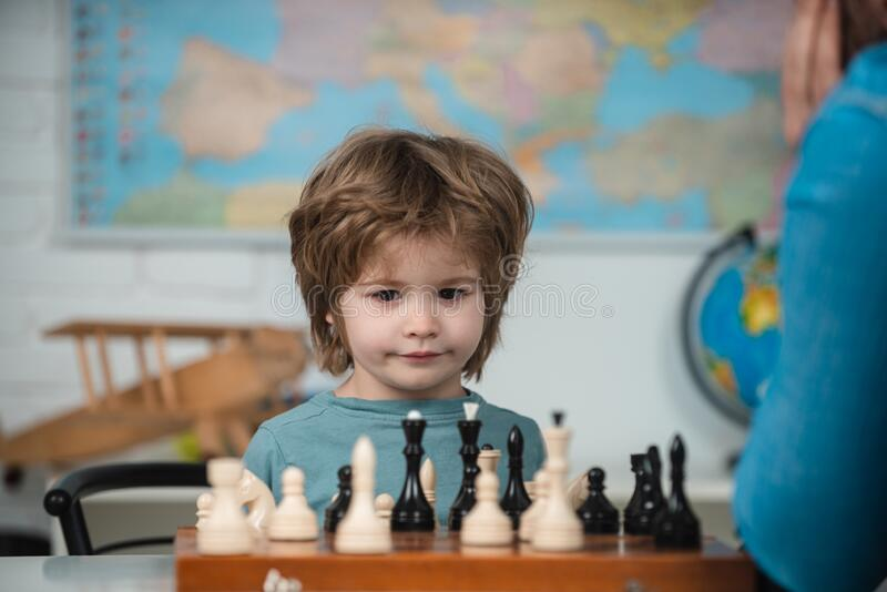 Happy child and childhood. Boy kid playing chess at home. Games and activities for children. Family concept. royalty free stock photography